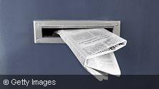 Eine Zeitung steckt in einem Briefkastenschlitz