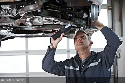 A car mechanic inspects the landing gear