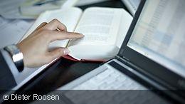 An open book next to a laptop