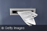 Newspaper sticking out of mail slot