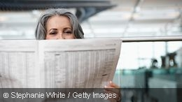 Woman sitting at the airport reading a newspaper